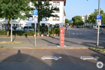 Das Bild zeigt eine Stromladesäule zwischen zwei öffentlichen Parkplätzen. Im Hintergrund zu sehen sind die Bushaltestellen am Reutlinger Hauptbahnhof.