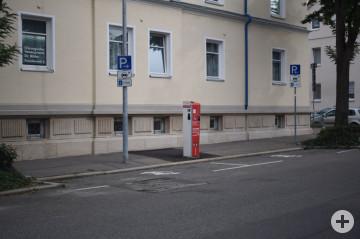Das Bild zeigt eine Stromladesäule zwischen zwei öffentlichen Parkplätzen.